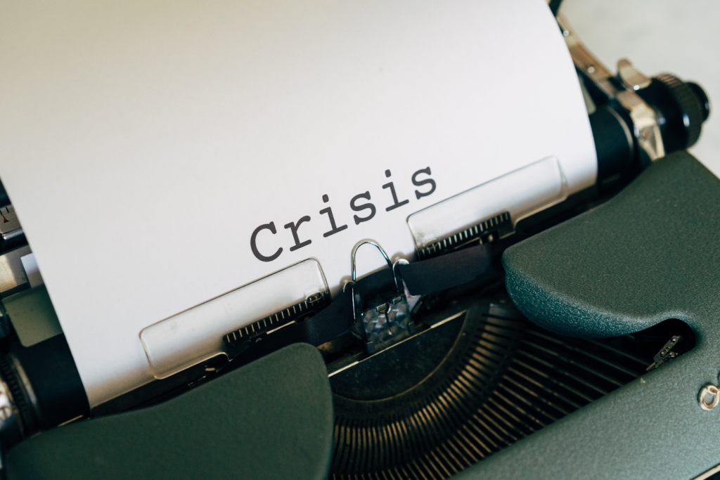 type writer with the word crisis typed out